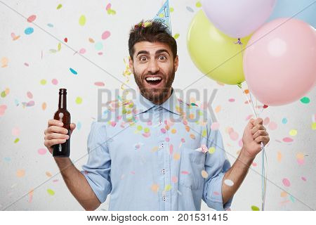 Happy Excited Man With Beard, Wearing Party Hat And Formal Clothes, Holding Bottle With Drink And Co