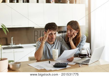 Depressed Young Caucasian Couple Calculating Family Budget In Kitchen, Trying To Find A Way To Make