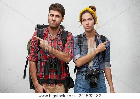 Female And Male Hitch-hikers Holding Huge Baggage In Their Rucksacks, Binoculars And Camera For Maki