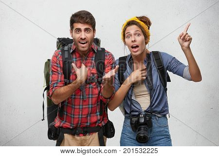 Portrait Of Agitated Young Couple With Rucksacks Gesturing Actively, Trying To Explain Themselves Wh