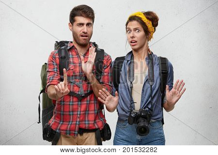 Studio Shot Of Emotional Bearded Guy And Beautiful Girl With Professional Camera Gesturing With Both