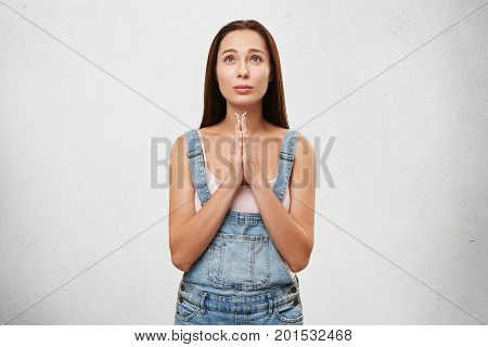 Young Female With Long Dark Straight Hair Looking Up Hopefully Praying With Her Hands Folded, Hoping