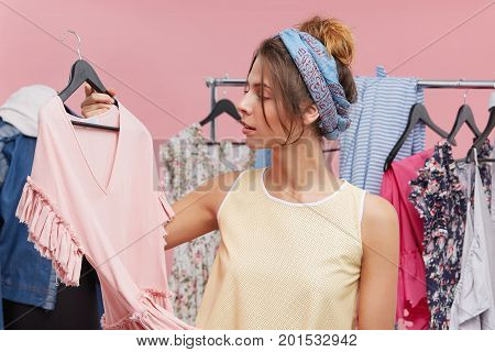 Young Woman Standing Near Her Wardrobe, Holding Dress On Hangers, Trying To Decide What To Wear On P