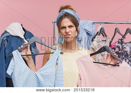 Young Beautiful Woman With Grumpy Expression, Frowning Her Face With Dissatisfaction While Holding T