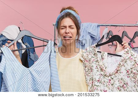 Pretty Woman Crying While Standing In Cloakroom, Holding Two Fashionable Dresses Of High Price, Havi