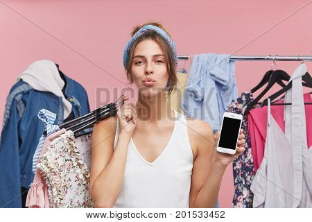 Pleased Female Model Pressing Her Lips, Standing Against Manequin And Rack With Clothes, Holding Hag