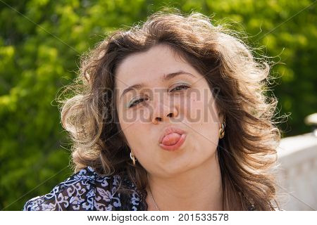 Emotional girl. Beautiful modern model shows tongue Positive woman hipster. Emotions on face.