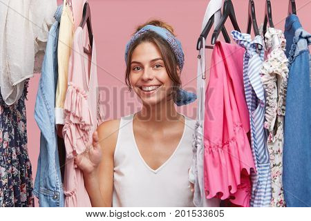 Positive Smiling Woman Wearing White T-shirt And Scarf, Looking Through Clothes Rail While Standing