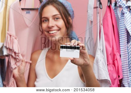 Shopping Time. Smiling Young Woman With Appealing Appearance, Standing Near Hangers With Clothes, De