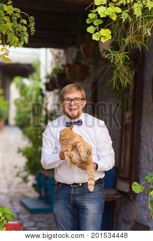 Red cat in the hands of stylish man.