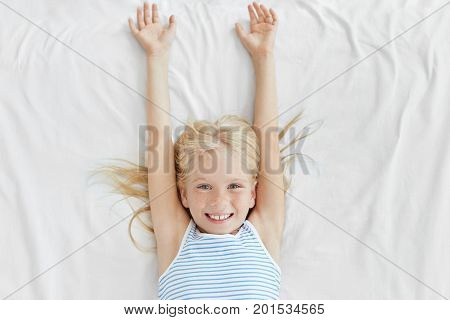 Adorable Little Girl With Blonde Hair And Freckles, Waking Up In Morning, Stretching On White Bedclo