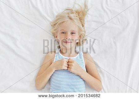 Cute Girl With Blonde Hair, Blue Charming Eyes And Freckled Face, Wearing Sailor T-shirt, Lying On W