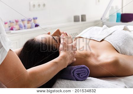 Face lifting massage in spa. Female beautician doctor with patient in wellness center. Professional cosmetologist make procedure to beautiful indian girl in cosmetology cabinet or beauty parlor. poster