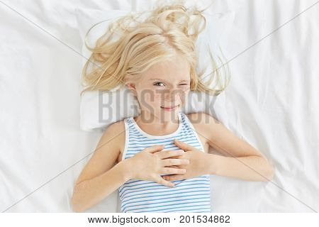 Children, Rest And People Concept. Lovely Little Girl With Long Blonde Hair, Closing One Eye While W