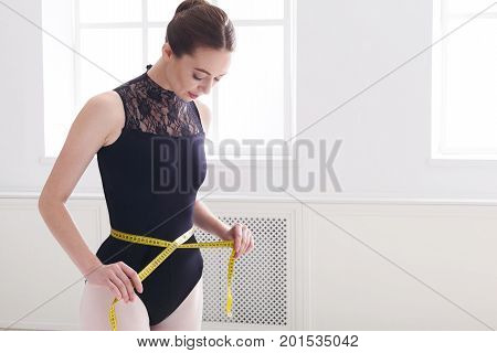 Ballerina looks at her perfect waist after diet. Beautiful graceful ballet dancer in black with measuring tape in light hall. Slimming and weight loss concept, copy space
