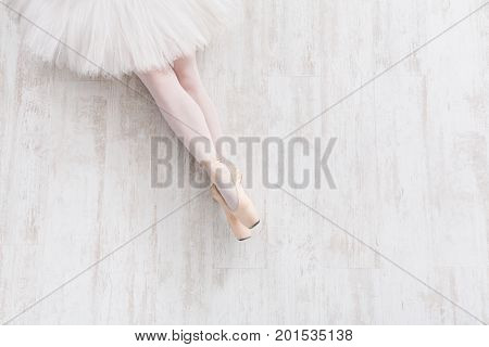 Ballet background with copy space top view, Young ballerina legs in pointe shoes at white wooden floor background, top view with copy space. Choreography and ballet practice concept
