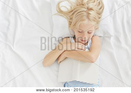 Small Kid With Beautiful Appearance Sleeping After Reading Interesting Stories In Bed, Keeping Book