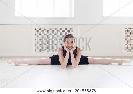 Beautiful ballerina doing side splits and smiling on camera. Classical ballet dancer at dancing class in white hall, copy space