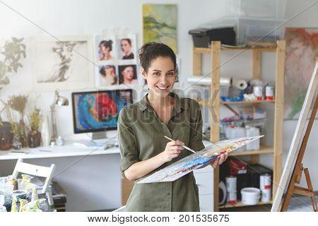 Indoor Shot Of Beautiful Brunette Female Painter Wearing Shirt, Holding Paint Brush In Hands Standin