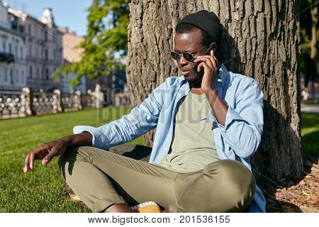 Outdoor Shot Of Dark-skinned Male In Trendy Glasses, Hat, Shirt And Trousers, Sitting Crossed Legs O