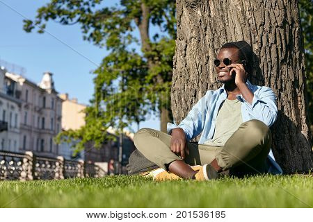 Stylish Black Hipster Male Wearing Sunglasses, Hat And Shirt With Trousers, Sitting Crossed Legs At
