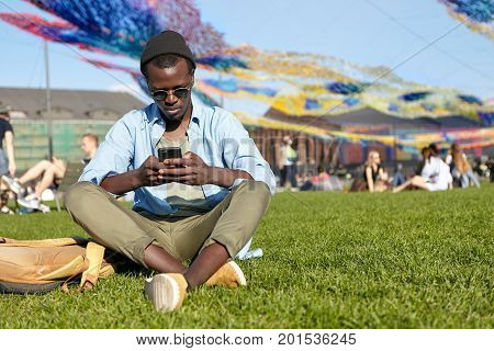 Restful Male With Dark Skin Wearing Black Hat, Sunglasses, Shirt, Trousers And Sport Shoes, Keeping