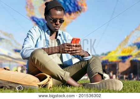Serious Dark-skinned Young Man In Trendy Shirt And Trousers, Relaxing On Green Lawn, Holding Red Sma