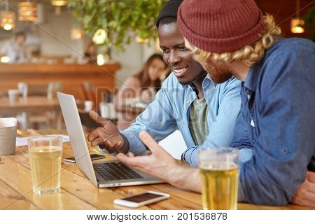 Two Stylish Male Entrepreneurs Of Different Races Drinking Beer While Having Business Meeting At Bar