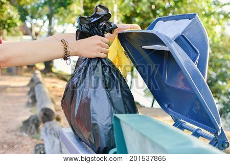 Close up female hand holding bin bag into the trash