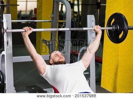 Brutal athletic man pumping up muscles on bench press.