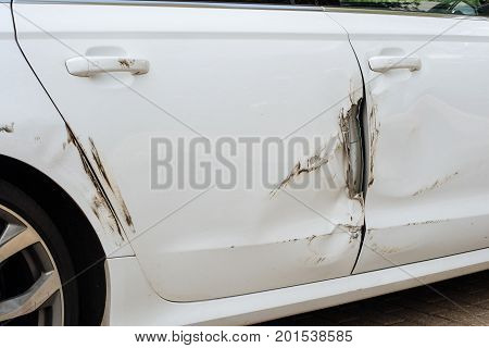 The right side of the car scratched with torn door metal after an accident