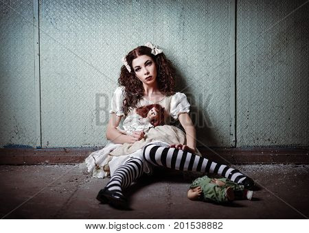 Portrait of a strange lonely girl with dolls in abandoned place