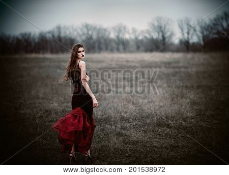 A beautiful sad girl in the field. Rear view