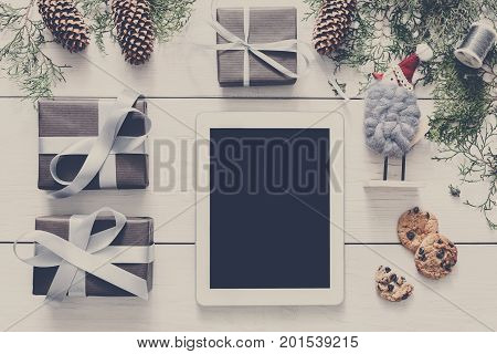 Christmas online shopping background. Tablet screen with copy space top view on white wood, present boxes and cookies. Electronic devices, internet commerce on winter holidays concept