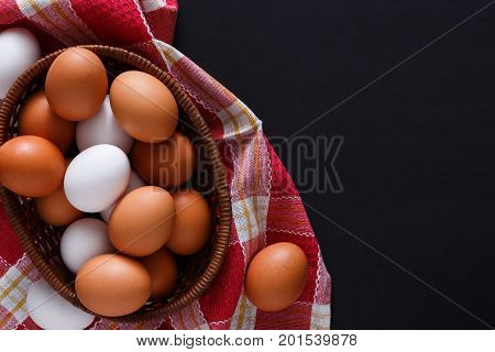 Poultry farm concept. Bowl with fresh brown and white eggs on cloth isolated on black background with copy space. Top view. Rural still life, natural organic healthy food.