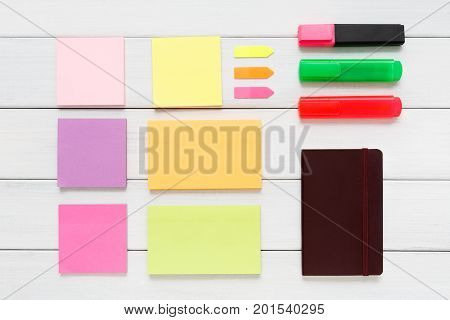 Flat lay of office and business stationery supplies - colorful markers, sticky notes and memo blocks, notepad, pen on white rustic wooden board background, top view with copy space, nobody, objects