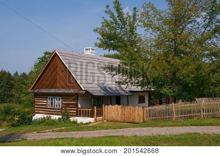 Typical timbered homestead with a saddle roof and a porch covered by the edge of the roof Air Open Museum in Kourim Czech Republic