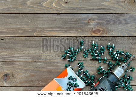 Roofing screws and a drill on a wooden table. The view from the top. Place for advertising and labels.Roofer roofing work.