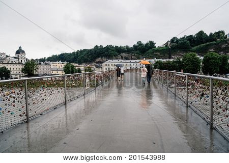 Salzburg Austria - August 6 2017: Scenic view of bridge with padlocks over river in Salzburg. The Old Town of Salzburg is internationally renowned for its baroque architecture and was listed as a UNESCO World Heritage Site.