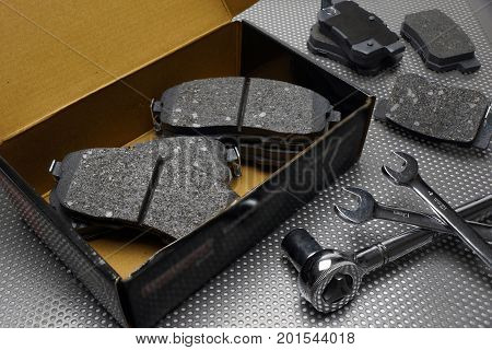 Front and rear wheel disc brake pads in a box on worktable