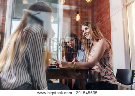 Cheerful girlfriends sitting and chatting in study room Shot through the window