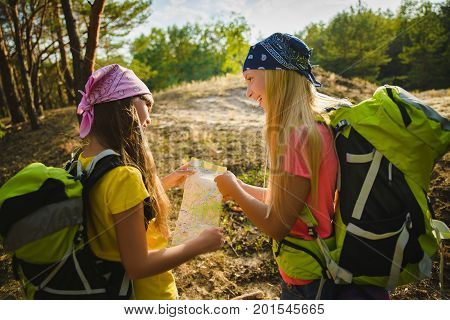 Girls with backpack looing at map. Adventure and travel or tourism concept.