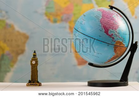 a small model of Big Ben side by side with USA-Earth globe on a blurred world map background