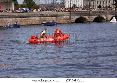 Red lifeguard rescue boat with lifeguards sailing in a channel with spectators on a bridge, Copenhagen, August 26, 2017
