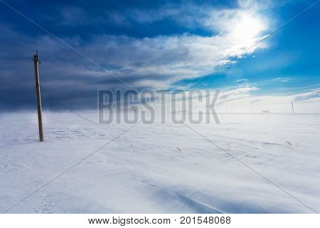 Broken phase electrical power lines on the electric poles on countryside in the winter during the storm and strong wind with snow. Russia. Island Sakhalin