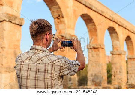 Photographer taking a picture of the ancient roman aqueduct of Tarragona Spain.
