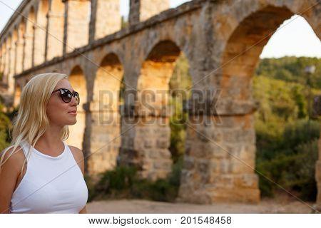 Woman posing near the roman Aqueduct Pont del Diable in Tarragona at sunset