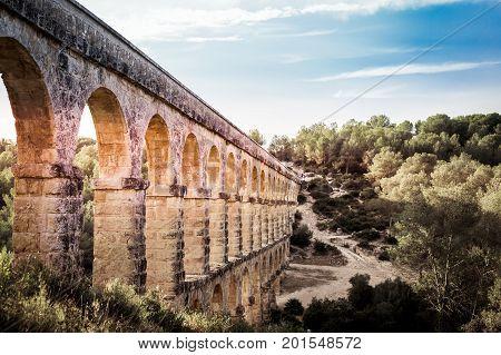 Beautiful View Of Roman Aqueduct Pont Del Diable In Tarragona At Sunset