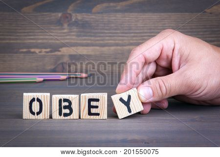Obey from wooden letters on wooden background.
