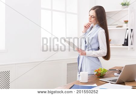 Confident young business woman in formalwear working on digital tablet while standing at office
